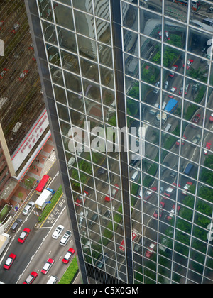 View looking down on Hong Kong streets below reflected in the glass windows of the Immigration Tower block - Stock Photo