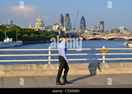 A man crossing Waterloo Bridge in the City of London taking a call on his mobile phone - Stock Photo