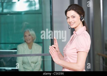 Germany, Munich, Woman wearing headset, business woman in background - Stock Photo