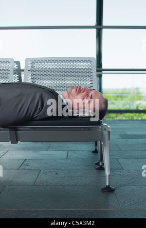 Germany, Leipzig-Halle, Businessman in Airport departure lounge, sleeping on bench - Stock Photo