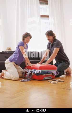 Germany, Leipzig, Couple trying to close suitcase - Stock Photo