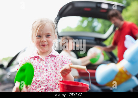 Germany, Leipzig, Parents loading luggage into car, girl (4-5) in foreground - Stock Photo