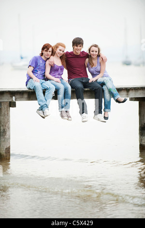 Germany, Bavaria, Ammersee, Four friends sitting on jetty - Stock Photo