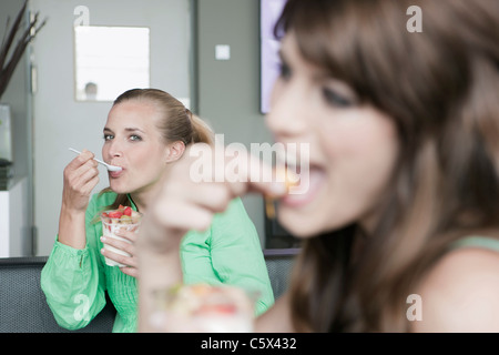 Germany, Cologne, Women in cafe, one eating a dessert, portrait - Stock Photo