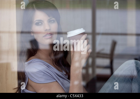 Germany, Cologne, Young woman sitting in window of cafe - Stock Photo
