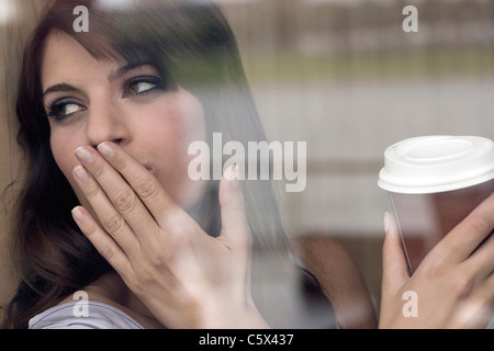 Germany, Cologne, Young woman in window of cafe - Stock Photo
