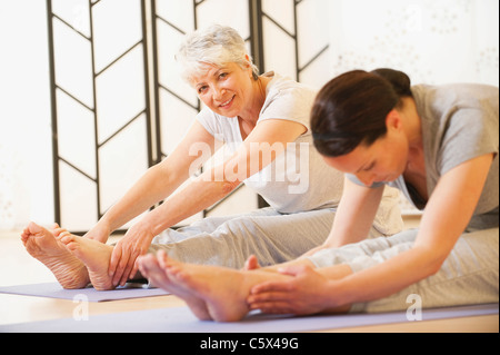 Two women doing exercise on mat, portrait - Stock Photo