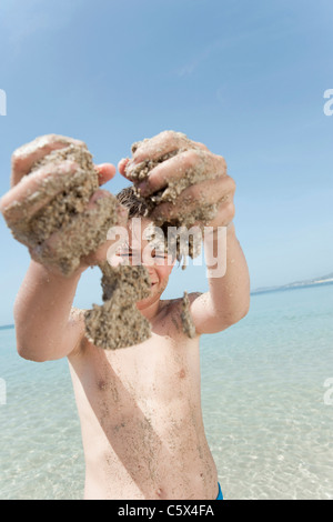 Spain, Mallorca, Boy (8-9) with sandy hands playing at the beach - Stock Photo