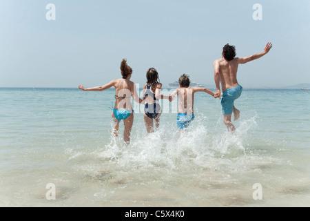 Spain, Mallorca, Family jumping into sea - Stock Photo