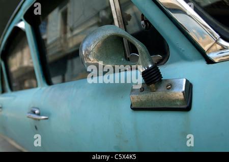Classic Cuban car detail showing a chrome wing mirror set against light blue paintwork. Seen in Havana Cuba. - Stock Photo