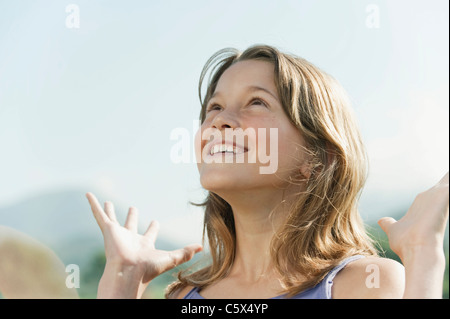 Spain, Mallorca, Girl (19-11) looking up, smiling, portrait - Stock Photo