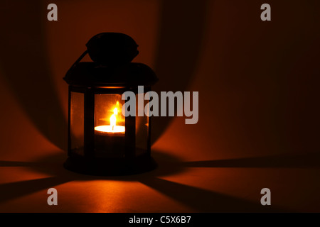 Lantern with burning candle in the dark