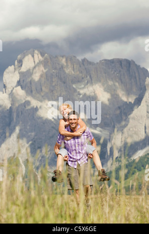 Italy, Seiseralm, Man carrying woman piggyback, laughing, portrait - Stock Photo