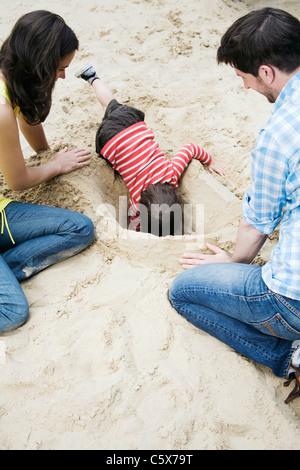 Germany, Berlin, Family and son (3-4) playing in sandbox - Stock Photo