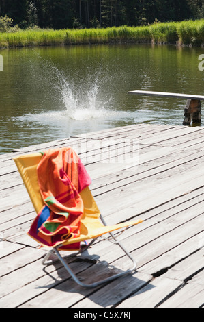 Italy, South Tyrol, Deserted deck chair on jetty - Stock Photo