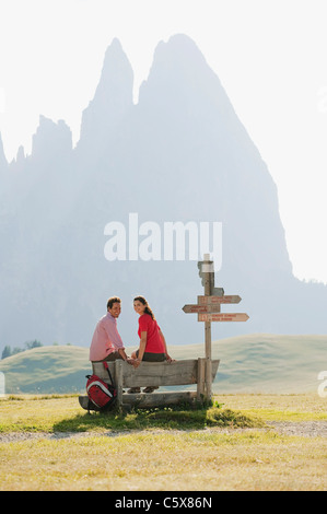 Italy, South Tyrol, Seiseralm, Couple sitting on bench - Stock Photo