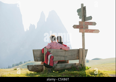 Italy, South Tyrol, Seiseralm, Couple sitting on bench, rear view - Stock Photo
