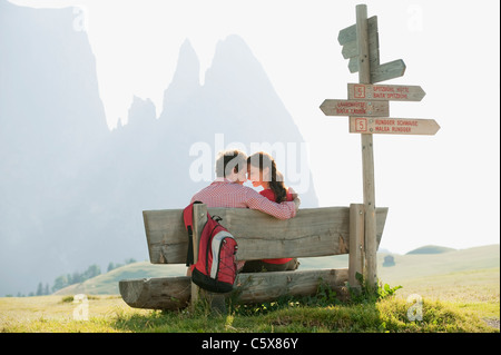 Italy, South Tyrol, Seiseralm, Couple sitting on bench, head to head - Stock Photo