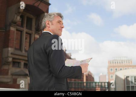 Germany, Hamburg, Businessman holding city map - Stock Photo