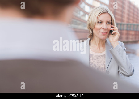 Germany, Hamburg, Person in foreground,  Business woman using mobile phone in background - Stock Photo