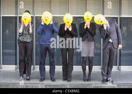 Germany, Hamburg, Five Business people standing in front of office building, hiding faces behind balloons - Stock Photo