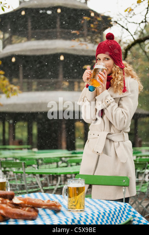 Germany, Bavaria, English Garden, Woman drinking beer in beer garden - Stock Photo