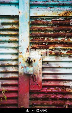 Metal entrance door with rusty padlock - Stock Photo