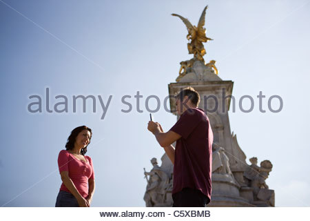 A young man taking a picture of his girlfriend in front of the Victoria Memorial - Stock Photo