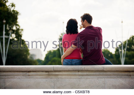 A young couple sitting on a wall, young man pointing at the London Eye - Stock Photo