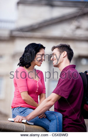 A young couple in front of Buckingham Palace, looking at each other - Stock Photo