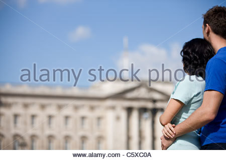 A young couple looking at Buckingham Palace - Stock Photo