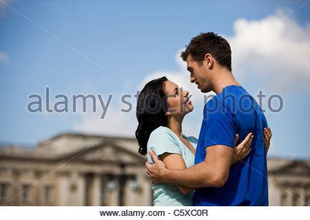 A young couple standing in front of Buckingham Palace - Stock Photo