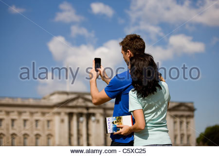 A young couple taking a picture of Buckingham Palace - Stock Photo
