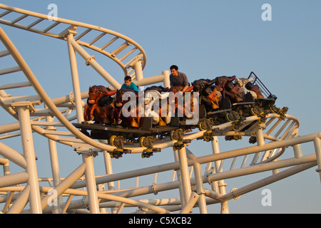 Visitors to Luna Park in Coney Island enjoy the new Steeplechase at sunset - Stock Photo