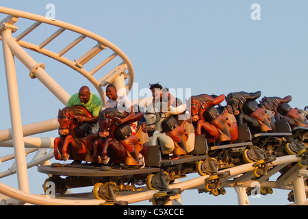 Visitors to Luna Park enjoy the new Stepplechase ride as the sun sets over Coney Island on a warm spring night - Stock Photo