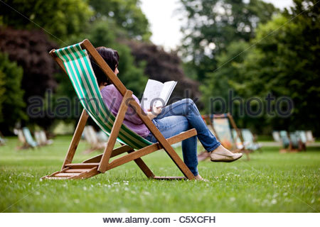 A young woman sitting on a deckchair in St James Park, looking at a guidebook - Stock Photo