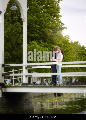 Kiss between boyfriend and girlfriend on a bridge in the Netherlands. Vertical shape, full length - Stock Photo