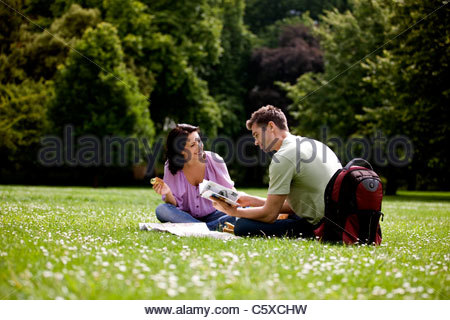 A young couple sitting on the grass, looking at a map and a guidebook - Stock Photo
