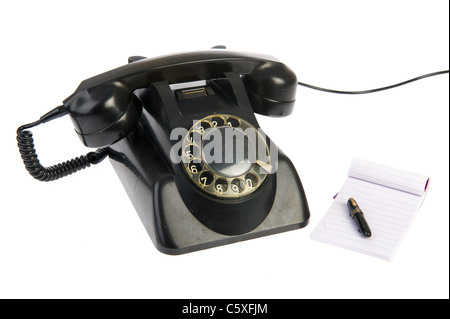 Vintage black telephone with memo pad isolated over white - Stock Photo