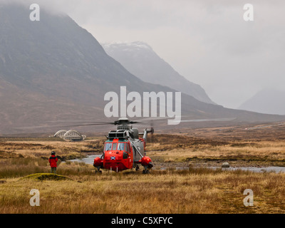 Crewman directs pilot of Royal Navy search and rescue helicopter as it lands at the head of Glencoe. - Stock Photo