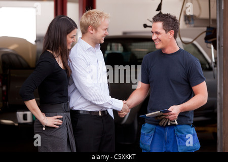 A happy attractive mechanic shaking hands with a customer couple,happy with their service - Stock Photo
