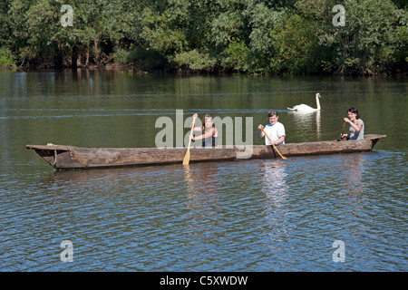 three girls in a dugout canoe, Archaeological Centre, Hitzacker, Nature Reserve Elbufer-Drawehn, Lower Saxony, Germany - Stock Photo