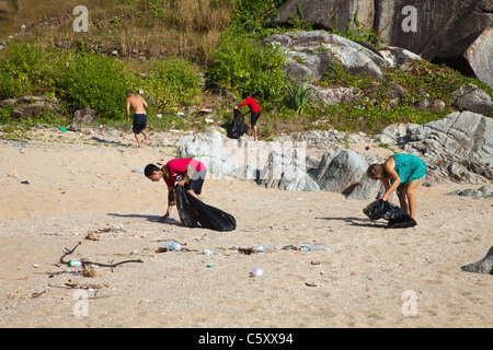 Thai schoolchildren schoolclass and volunteers cleaning Paradise Beach. - Stock Photo