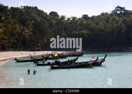 Holidaymakers swimming in clear water of the Andaman Sea at Freedom Beach and longtailboats anchored in bay. - Stock Photo