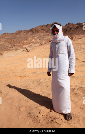 A Bedouin guide stands on sands in the Sinai Desert, Egypt. - Stock Photo