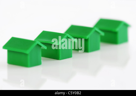 Four green model houses in a row - Stock Photo
