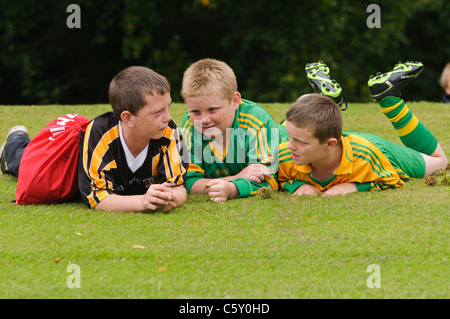 Three boys in GAA Gaelic Football outfit, lying on grass - Stock Photo