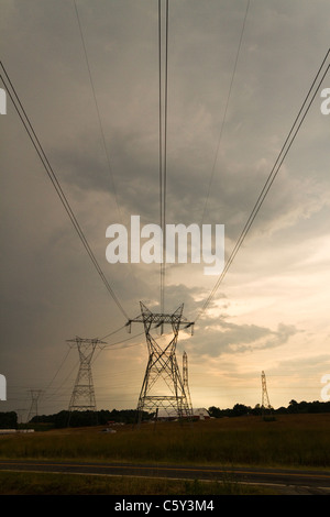 High Voltage power lines with a stormy sunset - Stock Photo