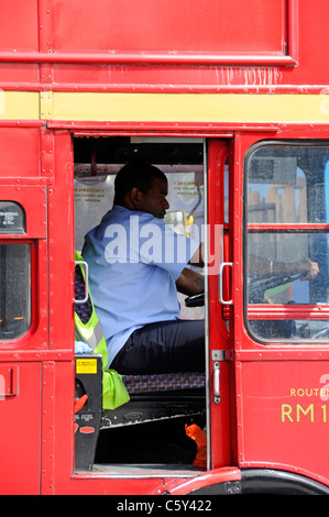 Hot summer day close up view of open door driver cab black man at work driving classic red double decker London - Stock Photo