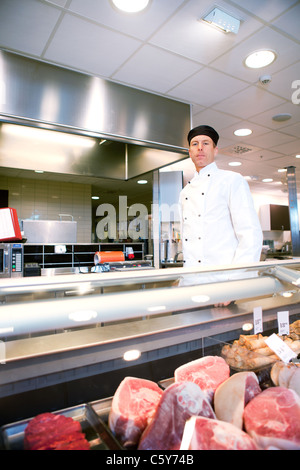 A serious satisfied butcher behind a fresh meat counter in a deli - Stock Photo